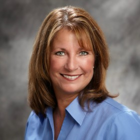 Portrait of Rachel Koenig wearing a blue collared shirt in front of a gray background