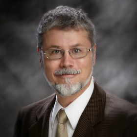 Portrait of Jim Hills wearing a dark suit, white shirt, tie, and rectangular glasses